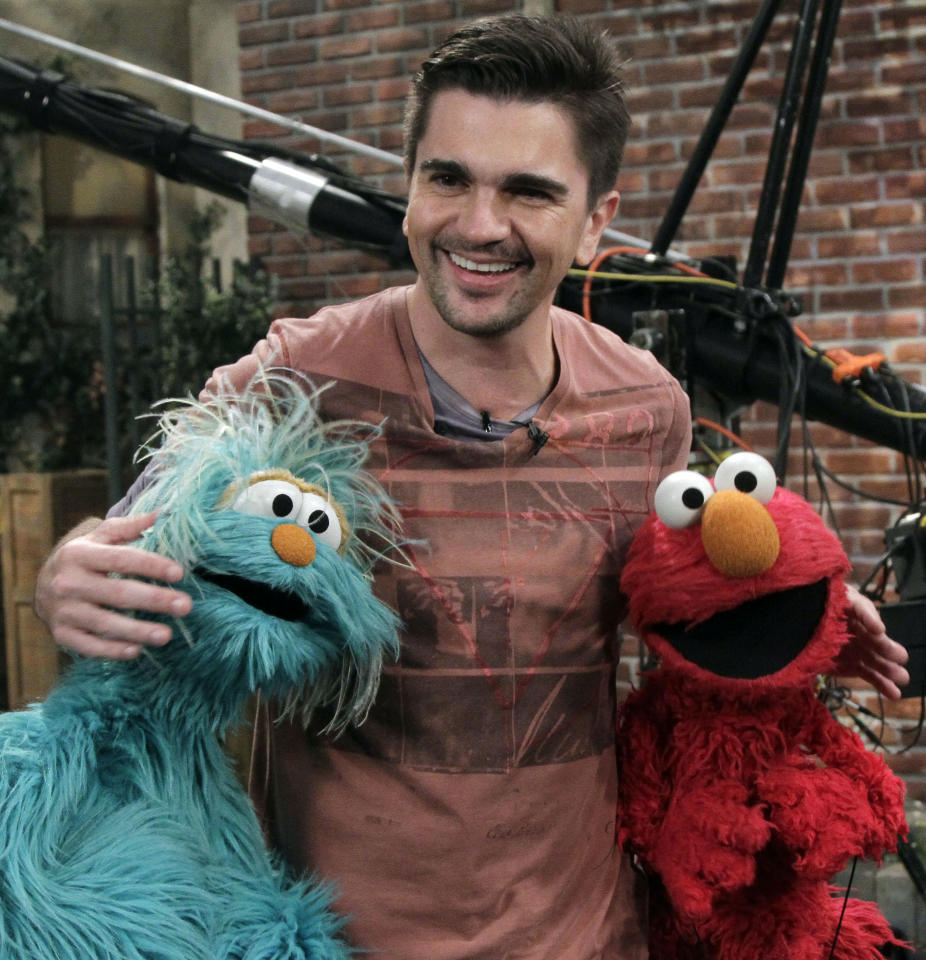 "Columbian musician Juanes poses for photos with Rosita, left, and Elmo on the set of ""Sesame Street,"" during the taping of his appearance on the show in New York, Monday, April 11, 2011."