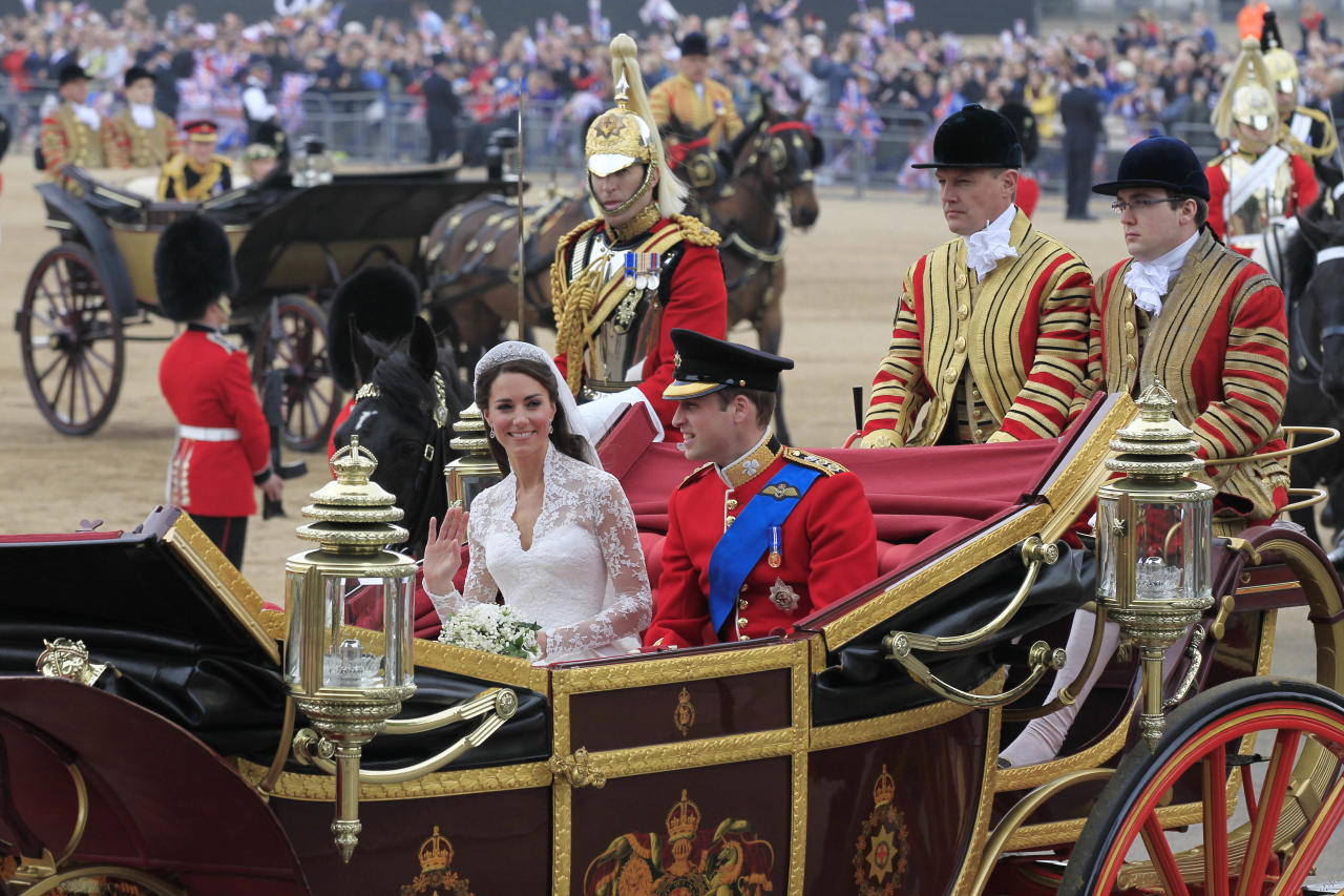 Britain's Prince William and his wife Kate, Duchess of Cambridge travel to Buckingham Palace on horse drawn carriage after their marriage at Westminster Abbey at the Royal Wedding in London, Friday, April 29, 2011.