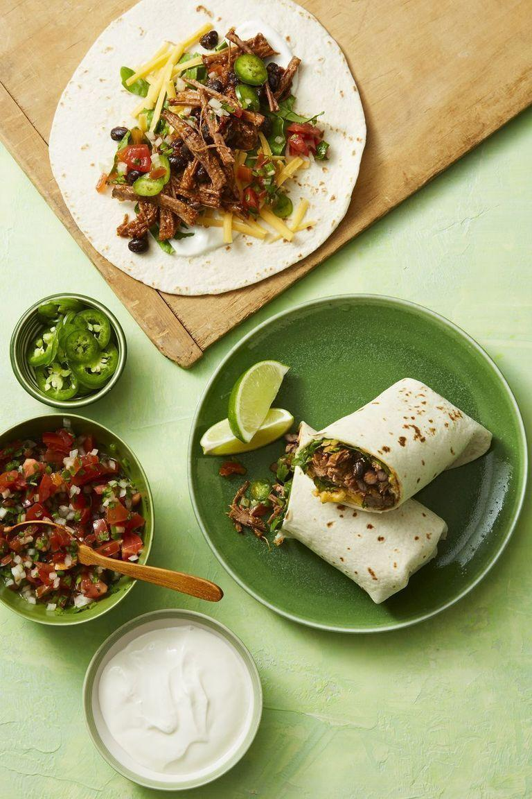 """<p>The best burrito fixings — saucy shredded beef and black beans — come together in <a href=""""https://www.goodhousekeeping.com/appliances/slow-cooker-reviews/g1996/top-rated-slow-cookers/"""" rel=""""nofollow noopener"""" target=""""_blank"""" data-ylk=""""slk:your slow cooker"""" class=""""link rapid-noclick-resp"""">your slow cooker</a> for an easy, hands-off dinner. </p><p><em><a href=""""https://www.womansday.com/food-recipes/food-drinks/a19779264/smoky-shredded-beef-burrito-recipe/"""" rel=""""nofollow noopener"""" target=""""_blank"""" data-ylk=""""slk:Get the recipe from Woman's Day »"""" class=""""link rapid-noclick-resp"""">Get the recipe from Woman's Day »</a></em></p>"""