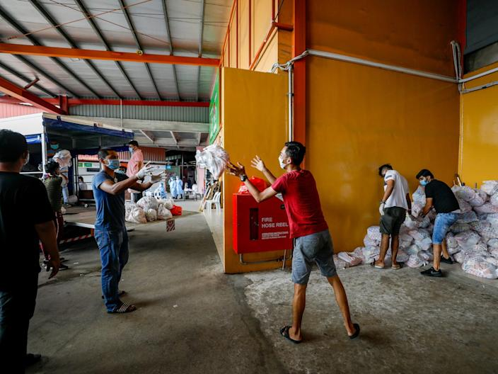 <br>Snacks are packed for migrant workers at S11 Punggol in Singapore on April 15, 2020.