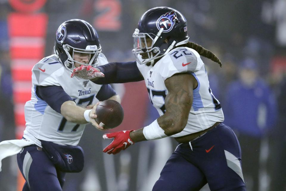 Tennessee Titans quarterback Ryan Tannehill, left, hands off to running back Derrick Henry in the first half of an NFL wild-card playoff football game against the New England Patriots, Saturday, Jan. 4, 2020, in Foxborough, Mass. (AP Photo/Charles Krupa)