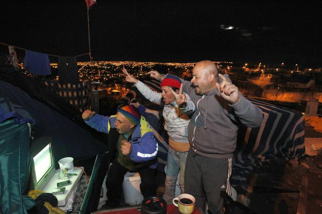 Fans of Chile celebrate the team's victory over Australia in their first 2014 World Cup match, as they watch the screening on a television outside their makeshift tent on the hills of Las Canas in Valparaiso city, northwest of Santiago June 13, 2014. Chile got the victory they needed if they are to have any chance of progressing from a daunting Group B when they held off a strong Australian fight back to emerge 3-1 winners in another open and entertaining World Cup clash on Friday. These fans are staying in temporary accommodation after their homes were destroyed in a fire that burned large swaths of predominantly low-income wooden houses in the hills in April. REUTERS/Eliseo Fernandez (CHILE - Tags: SPORT SOCCER WORLD CUP DISASTER)