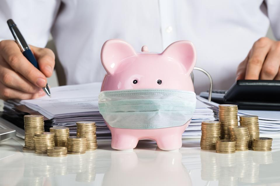 Midsection of businessman calculating invoice with piggybank and coins at office desk