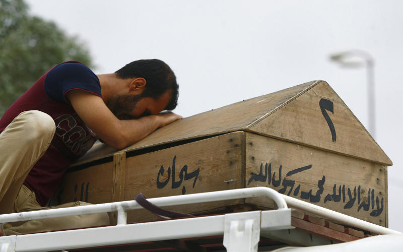 In this photo taken on Monday, May 20, 2013, Ali Karim weeps over his daughter's coffin before her burial in the holy Shiite city of Najaf, 160 kilometers (100 miles) south of Baghdad, Iraq. A wave of car bombings across Baghdad's Shiite neighborhoods and in the southern city of Basra killed and wounded dozens of people, police said. (AP Photo/ Alaa al-Marjani)