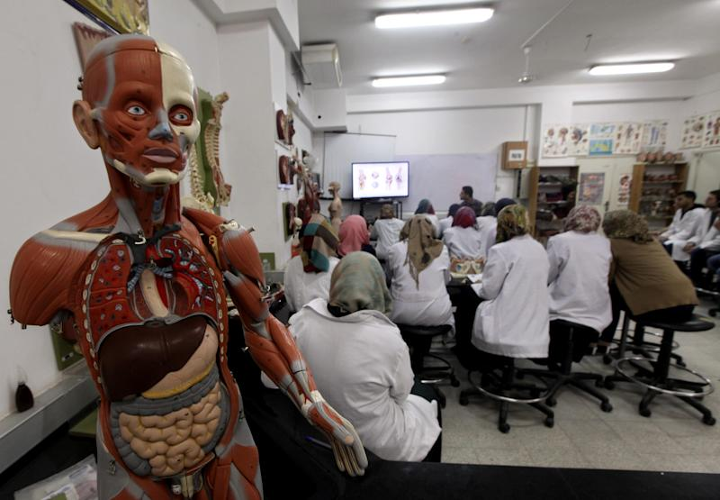 In this Wednesday, April 9, 2014 photo, Palestinian students listen to a lesson in the Faculty of Medicine at the Al-Quds University in the West Bank village of Abu Dis, near Jerusalem. Dozens of Palestinian doctors who graduated from Al-Quds University, a school that has a foothold in east Jerusalem, are caught in the political battle between Israel and the Palestinians over the city's eastern sector. Israel has refused to recognize the university's graduates -- a move that could amount to acknowledging the Palestinian claims to east Jerusalem as their capital. (AP Photo/Majdi Mohammed)