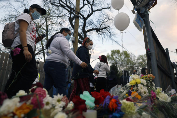 People pay tribute as they attend a peace walk honoring the life of police shooting victim 13-year-old Adam Toledo, Sunday, April 18, 2021, in Chicago's Little Village neighborhood. (AP Photo/Shafkat Anowar)