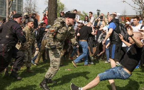 <span>A fighter of National Liberation Movement pushes a protester down, during clashes at a demonstration against President Vladimir Putin</span> <span>Credit: AP </span>