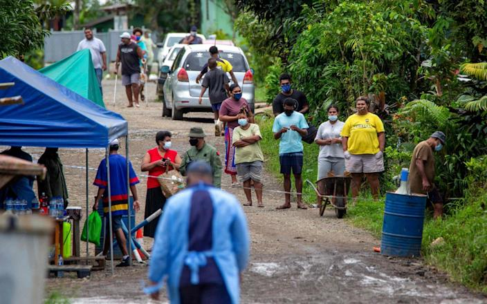 Residents look on as police check people are wearing face masks in Suva on July 3, 2021, as a worsening outbreak of the Covid-19 coronavirus Delta variant has overwhelmed the South Pacific nation's largest hospital - AFP