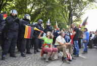 The participant in a demonstration against the Corona measures blows into a vuvuzela with a German and an Israeli flag in front of a police chain in Berlin, Germany, Saturday, Aug. 29, 2020. (Bernd Von Jutrczenka/dpa via AP)