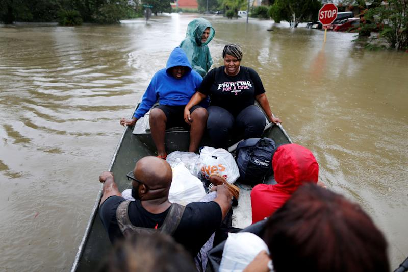 A family is rescued from rising floodwaters in the Beaumont Place community in southeast Texas on Monday. (Jonathan Bachman / Reuters)