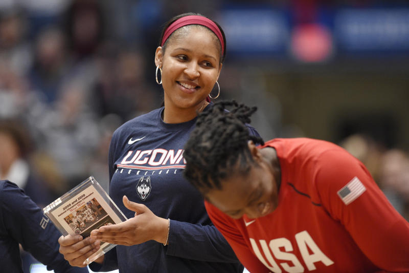 Minnesota Lynx' and former Connecticut player Maya Moore, shares a light moment with former teammate Tina Charles before a basketball game, Monday, Jan. 27, 2020, in Hartford, Conn. (AP Photo/Jessica Hill)