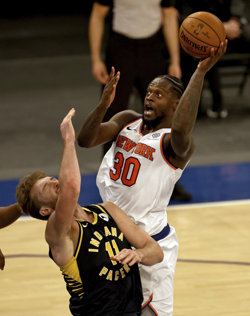 New York Knicks' Julius Randle (30) is called for an offensive foul as he collides with Indiana Pacers' Domantas Sabonis (11) in the fourth quarter of an NBA basketball game Saturday, Feb. 27, 2021, in New York. (Elsa/Pool Photo via AP)