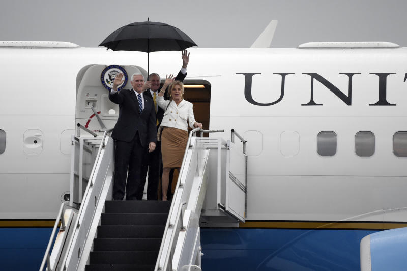 Vice President Mike Pence, left, arrives at Joint Base Charleston with South Carolina Gov. Henry McMaster, center, and his wife, Peggy, Thursday, Feb. 13, 2020, in North Charleston, S.C. (AP Photo/Meg Kinnard