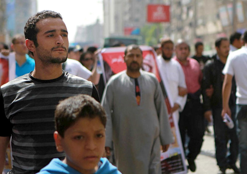 FILE - In this April 1, 2011 file photo, activist Ahmed Douma, left, during a march to Tahrir Square demanding prosecution of members of former President Hosni Mubarak's regime in Cairo, Egypt.  Egypt's state news agency says judges have decided to keep a Douma in detention until June 3, when a verdict is expected on a charge of insulting the country's president. (AP Photo/Sarah Carr, File)