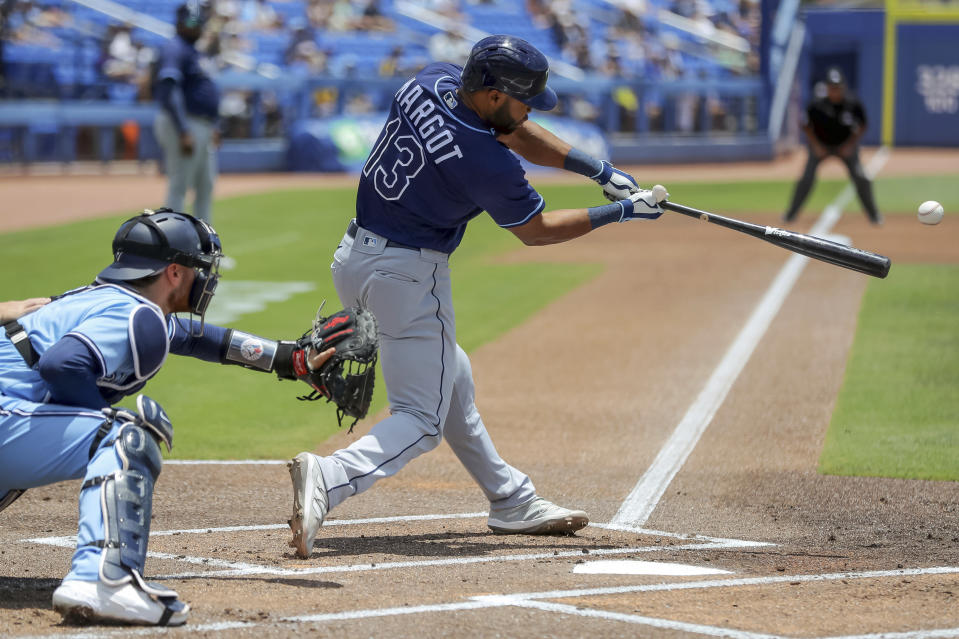 Tampa Bay Rays' Manuel Margot (13) hits an RBI-single to score Randy Arozarena in front of Toronto Blue Jays catcher Danny Jansen, left, during the first inning of a baseball game Sunday, May 23, 2021, in Dunedin, Fla. (AP Photo/Mike Carlson)