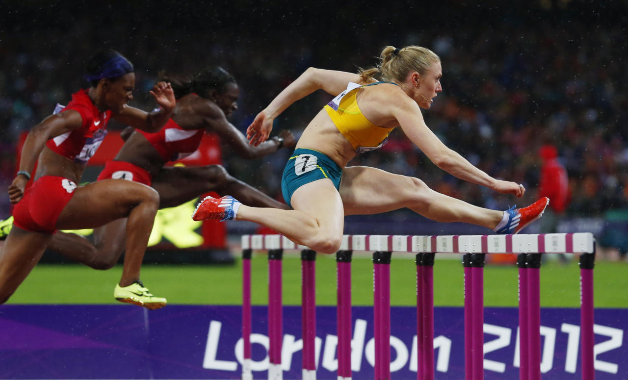 Australia's Sally Pearson (R) clears a hurdle ahead of Dawn Harper (C) and Kellie Wells of the U.S. in the women's 100m hurdles final during the London 2012 Olympic Games at the Olympic Stadium August 7, 2012. Pearson won gold and set a new Olympic record. REUTERS/Eddie Keogh (BRITAIN  - Tags: SPORT OLYMPICS SPORT ATHLETICS TPX IMAGES OF THE DAY)