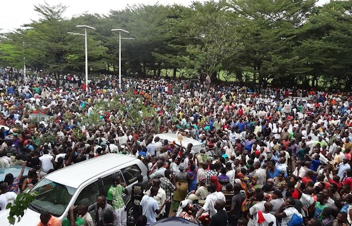 """Burundians gather outside the headquarters of the popular independent African Public Radio (RPA) in Bujumbura to welcome the release on bail of its director director accused of """"complicity"""" in the murder of three Italian nuns, on February 18, 2015 (AFP Photo/Esdras Ndikumana)"""