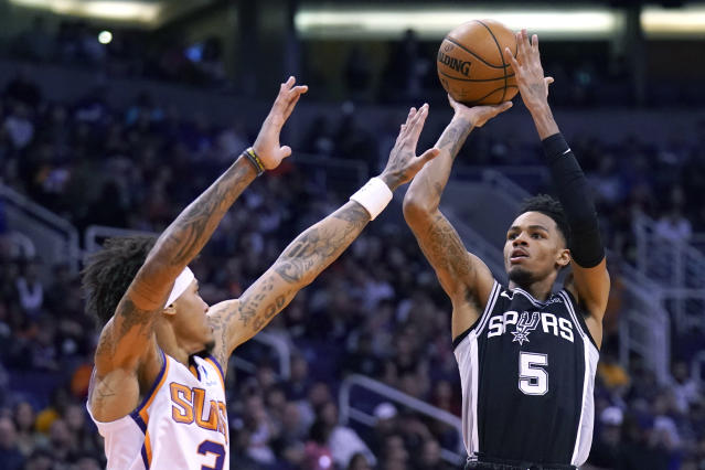 San Antonio Spurs guard Dejounte Murray (5) shoots over Phoenix Suns forward Kelly Oubre Jr. during the first half of an NBA basketball game Monday, Jan. 20, 2020, in Phoenix. (AP Photo/Rick Scuteri)