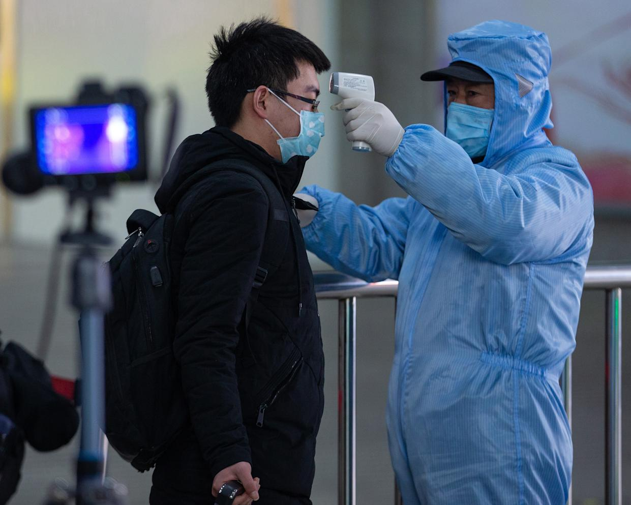 A Chinese worker wearing the protective clothing checks passenger's body temperatures for prevention of the new coronavirus and pneumonia at the exit of Nanjing Railway Station during the Chinese New Year or Spring Festival holiday in Nanjing City, east China's Jiangsu Province on January 29th, 2020. (Photo by Su Yang / Costfoto/Sipa USA)