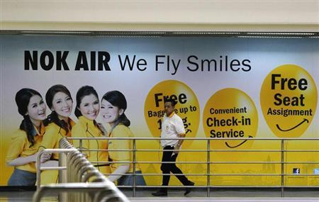 A Nok Air staff member walks past a commercial for the airlines at Don Muang International Airport in Bangkok