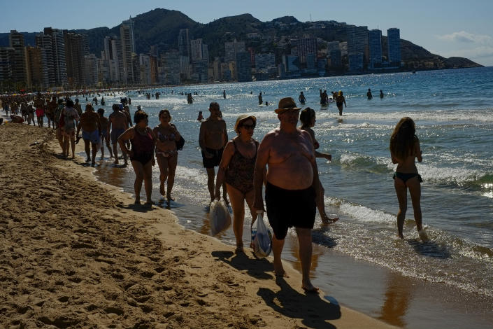 FILE - In this June 25, 2021, file photo, people walk along the beach on a summer's day in Benidorm, southeast Spain. Countries across Europe are scrambling to accelerate coronavirus vaccinations to outpace the spread of the delta variant in a high-stakes race to prevent hospital wards from filling up again with patients fighting for their lives. (AP Photo/Alvaro Barrientos, File)