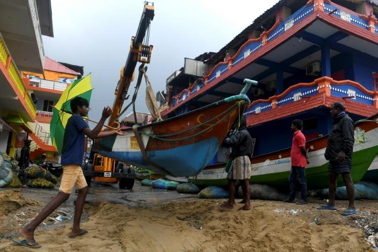 Fishermen in Mahabalipuram move their boats as Cyclone Nivar approaches the eastern Indian coast on November 24, 2020