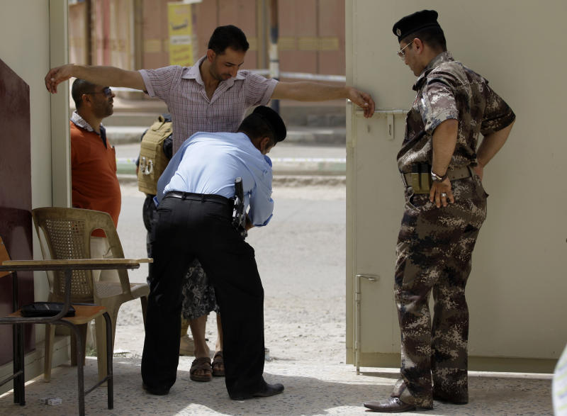 An Iraqi policeman searches a man as he enters a polling center during the country's provincial elections in Fallujah, Iraq, Thursday, June 20, 2013. Iraqis in two Sunni-dominated provinces voted Thursday in provincial elections marked by tight security measures that left streets in former insurgent strongholds largely deserted. (AP Photo/ Khalid Mohammed)