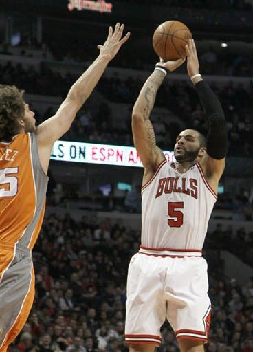 Chicago Bulls forward Carlos Boozer (5) shoots over Phoenix Suns center Robin Lopez during the first half of an NBA basketball game Tuesday, Jan. 17, 2012, in Chicago. (AP Photo/Charles Rex Arbogast)