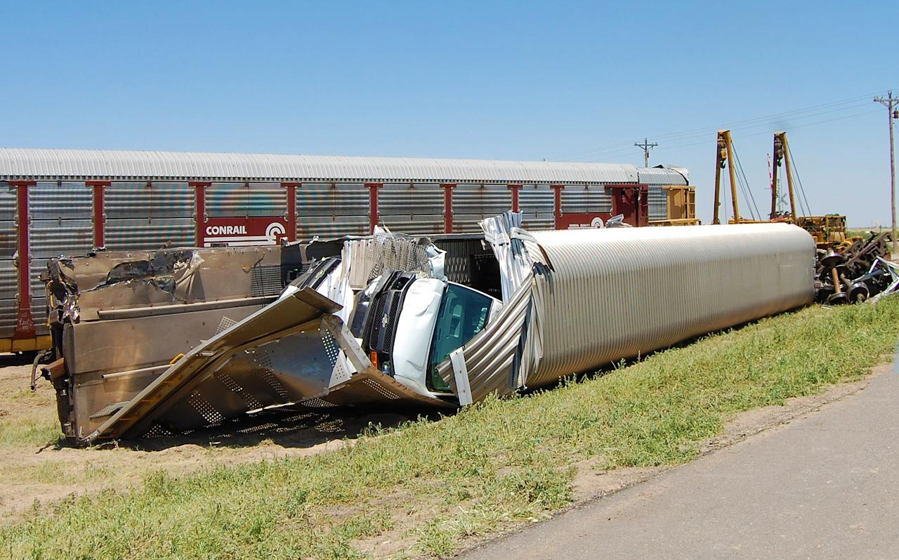A van that was part of the cargo being hauled by a Union Pacific train is is seen in the wreckage on Monday, June 25, 2012, near Goodwell, Okla. Two Union Pacific locomotives collided Sunday, June 24, 2012, two miles outside Goodwell, Okla., killing two crew members and a conductor. (AP Photo/The Guymon Daily Herald, Trudy Hart)