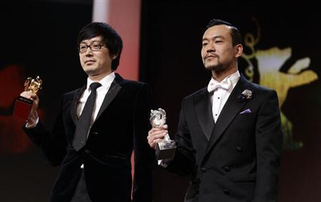 """Diao Yinan (L) director of """"Bai Ri Yan Huo"""" (Black Coal, Thin Ice) poses with his Golden Bear for Best Film next to actor Liao Fan (R) who poses with his Silver Bear for Best Actor, during the awards ceremony of the 64th Berlinale International Film Festival in Berlin February 15, 2014. REUTERS/Tobias Schwarz"""