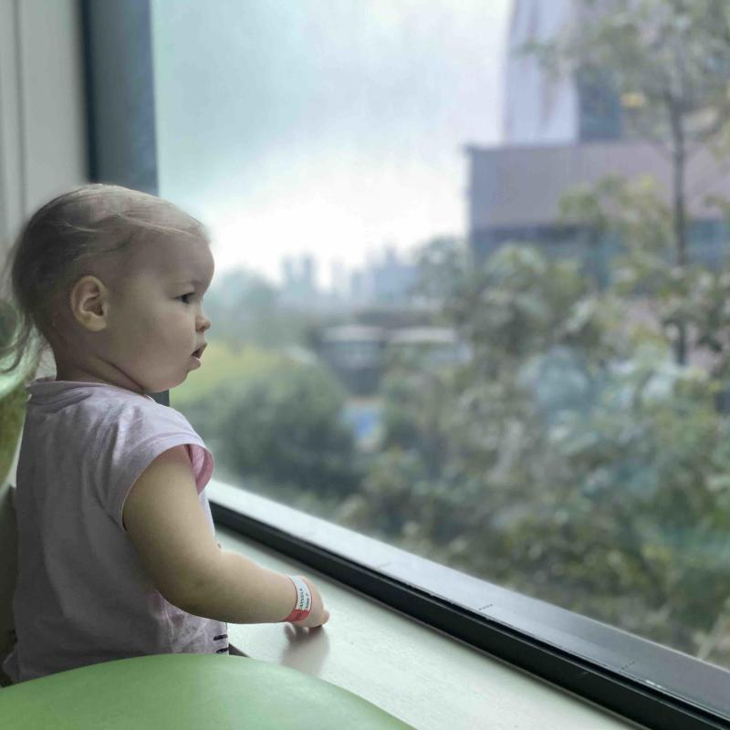 Chloé stares out of her hospital window. Her hair has begun to fall out after chemotherapy. Source: supplied
