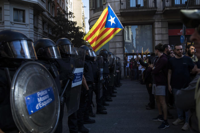 Catalan police officers cordon off the street to stop pro independence demonstrators, on their way to meet demonstrations by members and supporters of National Police and Guardia Civil in Barcelona on Saturday, Sept. 29, 2018. (AP Photo/Emilio Morenatti)