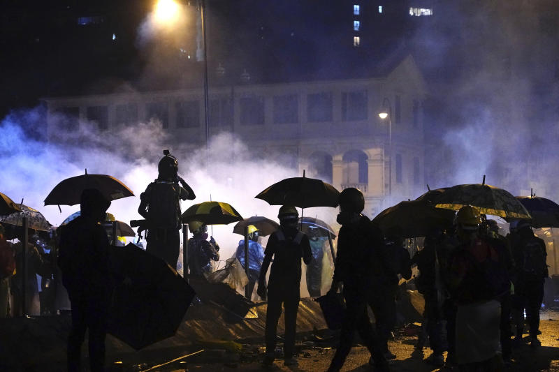 Protesters stand outside of Hong Kong Polytechnic University after police gave protesters an ultimatum to leave the campus in Hong Kong, early Monday, Nov. 18, 2019. Police launched a late-night operation Sunday to try to flush about 200 protesters out of a university campus on a day of clashes in which an officer was hit in the leg with an arrow and massive barrages of tear gas and water cannons were fired. (AP Photo/Vincent Yu)
