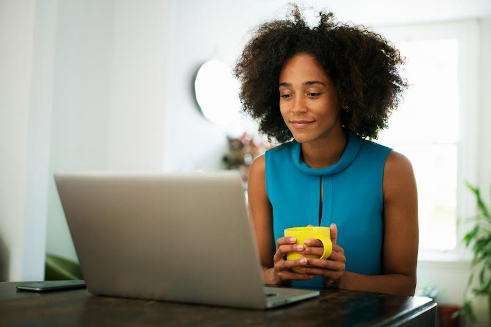 Woman looking at laptop with cup of coffee