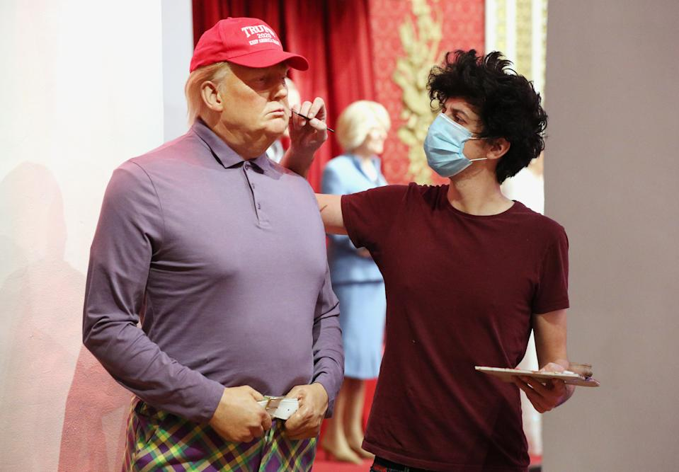 A member of the Madame Tussauds studios team adjusts a wax figure of Donald Trump which has been re-dressed in golf wear following the 2020 US presidential election, after Joe Biden's third bid for the White House has been a success as he is set to become the 46th President of the United States. (Photo by Jonathan Brady/PA Images via Getty Images)
