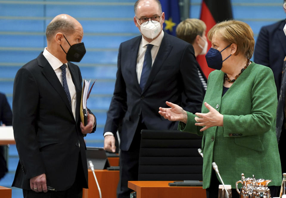 German Finance Minister Olaf Scholz, left, and German Chancellor Angela Merkel, right, talk as they arrive for the weekly cabinet meeting at the Chancellery in Berlin, Germany, Wednesday, May 12, 2021. (AP Photo/Michael Sohn)