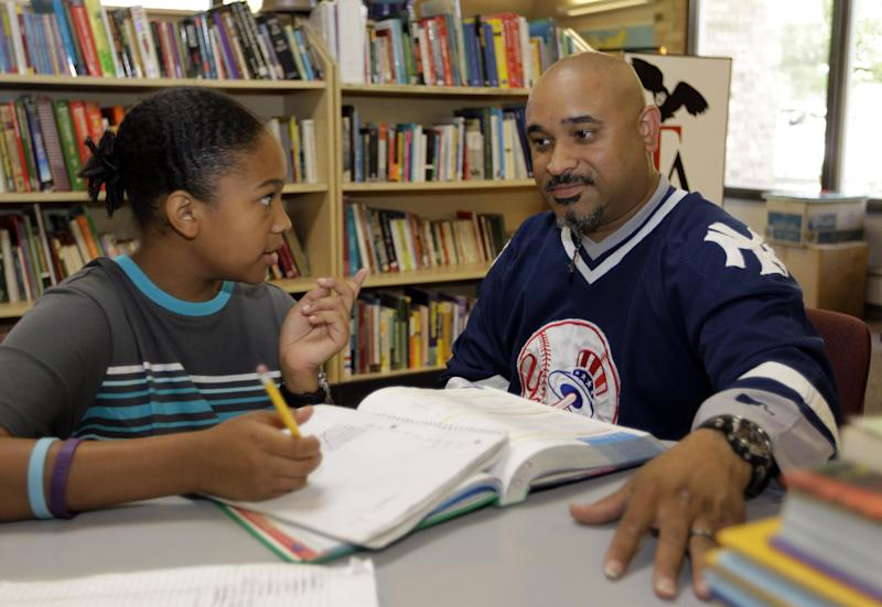 In this Aug. 7, 2012 photo, Phillip Covington, right, talks with his son Giovanni as he works on a mathematics lesson in the library of Todd Academy in Indianapolis. Struggling Indiana public school districts are buying billboard space, airing radio ads and even sending principals door-to-door in an unusual marketing campaign aimed at persuading parents not to move their children to private schools as the nation's largest voucher program doubles in size. (AP Photo/Michael Conroy)