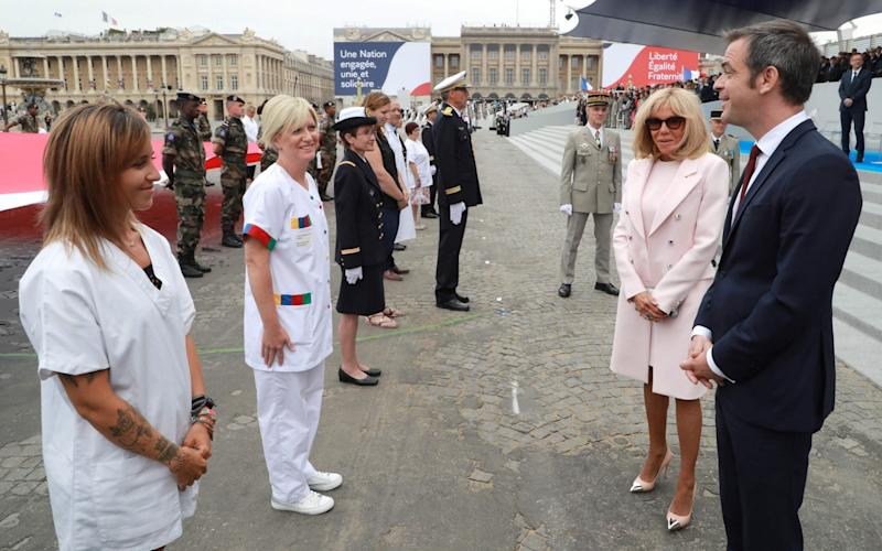 French health minister Olivier Veran (R) and French First Lady Brigitte Macron (rear R) speak to members of the medical staff - LUDOVIC MARIN/AFP