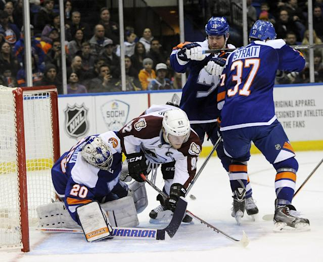 Colorado Avalanche's Gabriel Landeskog (92) crashes into New York Islanders goalie Evgeni Nabokov (20) leaving the puck behind for Avalanche Nathan MacKinnon to score as Islanders' Eric Boulton (36) and Brian Strait (37) try to defend in the first period of an NHL hockey game on Saturday, Feb. 8, 2014, in Uniondale, N.Y. (AP Photo/Kathy Kmonicek)