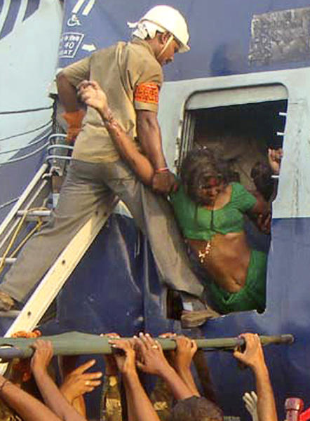 ALTERNATE CROP OF DEL114 - Rescuers evacuate an injured woman from the site of a train accident at a station near Penukonda, about 170 kilometers (105 miles) north of Bangalore, India, Tuesday, May 22, 2012. The passenger train rammed into a parked freight train and burst into flames before dawn Tuesday, killing more than a dozen people in southern India, officials said. (AP Photo)