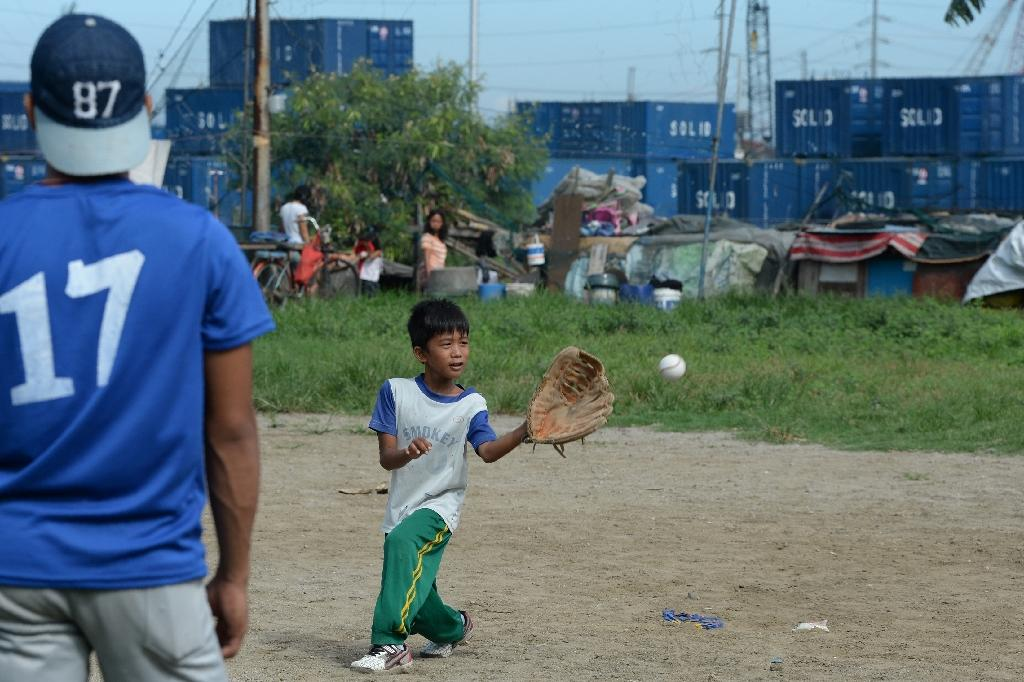 Slum residents are seen in the background as a young member of the Smokey Mountain baseball team trains on the former landfill (AFP Photo/Ted Aljibe)