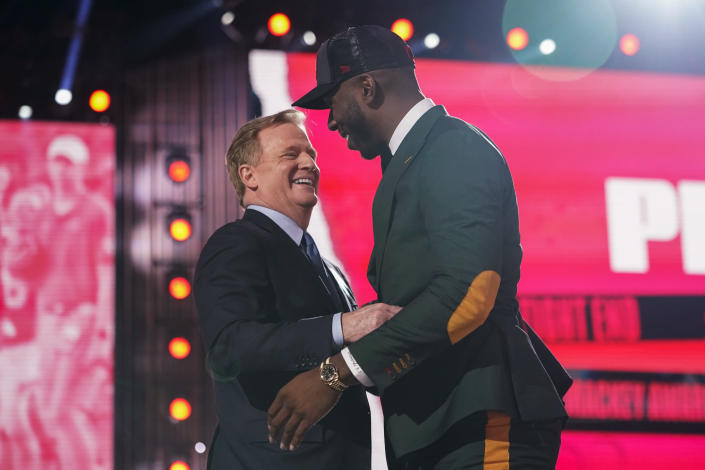 Florida tight end Kyle Pitts, right, is greeted by NFL Commissioner Roger Goodell after he was chosen by the Atlanta Falcons with the fourth pick in the NFL football draft Thursday, April 29, 2021, in Cleveland. (AP Photo/Tony Dejak)