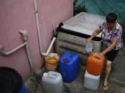 Nanceli, 61, fills a bucket with rainwater she collects from a water box, for use in the bathroom and to clean the floor of her house in Brasilandia slum, in Sao Paulo February 10, 2015. REUTERS/Nacho Doce