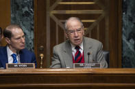 FILE - In this Tuesday, Jan. 29, 2019, file photo, Sen. Chuck Grassley, R-Iowa, center, chairman of the Senate Finance Committee, is joined at left by Sen. Ron Wyden, D-Ore., the ranking member, at a hearing on the high price of prescription drugs, on Capitol Hill in Washington. A bipartisan congressional investigation released Wednesday, Dec. 16, 2020, by Grassley and Wyden, found that key players in the nation's opioid industry have spent $65 million since 1997 funding nonprofits that advocate treating pain with medications, a strategy intended to boost the sale of prescription painkillers. (AP Photo/J. Scott Applewhite, File)