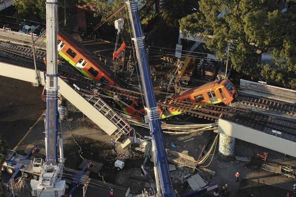 An aerial view of subway cars dangle at an angle from a collapsed elevated section of the metro
