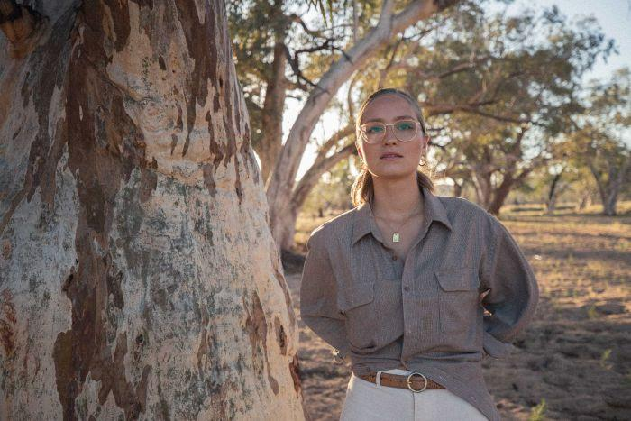 A woman wearing glasses standing next to a big tree