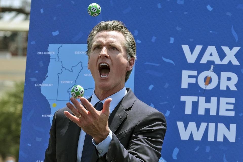 """California Gov. Gavin Newsom juggles balls with winning numbers after the Vax for the Win lottery contest during a news conference at Universal Studios in Universal City, Calif., Tuesday, June 15, 2021. On Tuesday, California lifted most of its COVID-19 restrictions and ushered in what has been billed as the state's """"Grand Reopening."""" (AP Photo/Ringo H.W. Chiu)"""