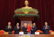 Vietnam Communist party General Secretary Nguyen Phu Trong, center left, is presented with a bouquet by Prime Minister Nguyen Xuan Phuc, center right, in Hanoi, Vietnam, Sunday, Jan. 31, 2021. Vietnam Communist Party has re-elected Nguyen Phu Trong for another term as the party's General Secretary, the country de-facto top leader. Other officials from left; Vo Van Thuong, Secretary of the Central Committee, Pham Minh Chinh, head of the Central Organization Committee and Vuong Dinh Hue, Hanoi Secretary of the Communist Party (Le Tri Dung/VNA via AP)