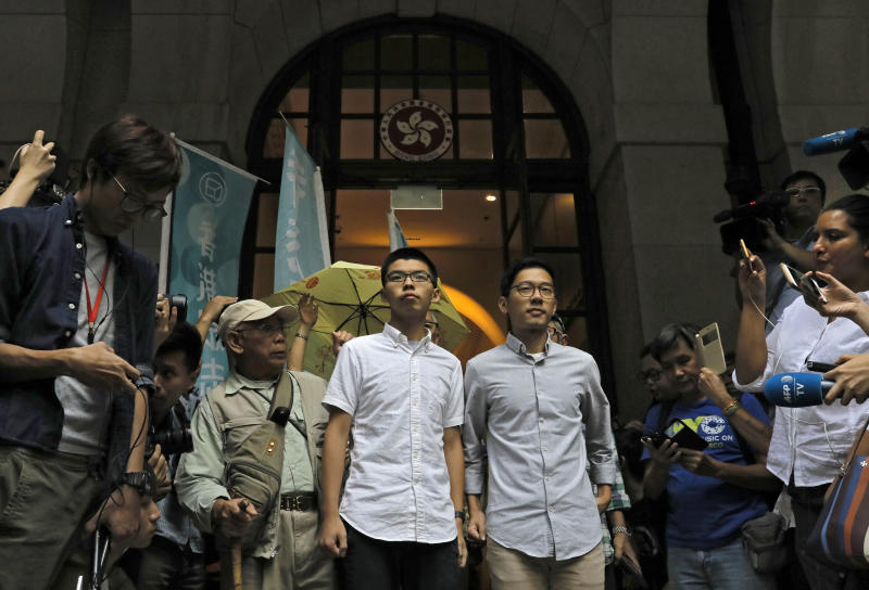 Pro-democracy activists Joshua Wong, center left, and Nathan Law, center right, walk out of the Court of Final Appeal Hong Kong, Tuesday, Oct. 24, 2017. Hong Kong's highest court freed the pro-democracy activists on bail pending an appeal of their prison sentences after they were convicted of sparking massive protests in 2014. (AP Photo/Vincent Yu)