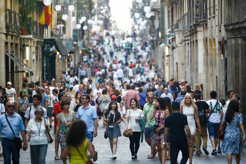 People stroll down a street in the city-center of Barcelona on June 28, 2015 (AFP Photo/Quique Garcia)